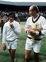 Stan Smith leaves the court with the Men's Singles Trophy, Ilie Nastase leaves looking dejected. Mens Singles Final. Wimbledon Tennis Championship, 1972. Credit: Colorsport.