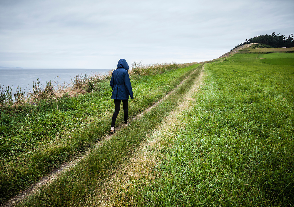 A young woman walking on the trail to Ebby Bluffs, Ebey's Landing National Historical Reserve, Whidbey Island, Washington, USA.
