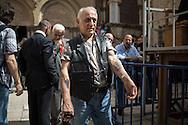 Un pellegrino fuori al portone del Santo Sepolcro mostra i tatuaggi sugli avambracci. Ha sceto tra le figure piu complesse e, tra i pochi a colori. Come si puo vedere dalle date ogni anno aggiunge un pellegrinaggio ed un tatuaggio