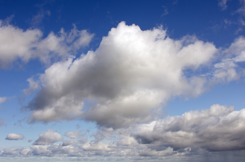 Fluffy white clouds in a deep blue sky.