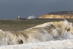 © Licensed to London News Pictures. 07/02/2016. Seaford, East Sussex UK. Huge waves are seen on Seaford beach in front of the white cliffs and lighthouse at Newhaven in east Sussex during gales and stormy weather this morning. Yellow weather warnings are in place for the south of England and many parts of the UK. Photo credit : Vickie Flores/LNP