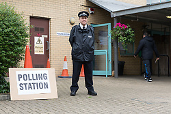 © Licensed to London News Pictures. 22/05/2014. London, UK. A police officer stands outside a polling station at Blue Gate Fields Junior School in Shadwell, East London on 22 May 2014.  All polling stations in Tower Hamlets today have a police presence to protect voters from any intimidation. Photo credit : Vickie Flores/LNP