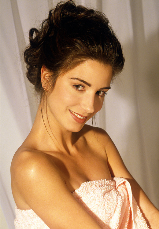 Close up of smiling woman with hair up in stylized bathroom with towel around herself