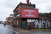 Community is kindness billboard sign in Digbeth in Birmingham city centre, which is virtually deserted under Coronavirus lockdown on a wet rainy afternoon on 28th April 2020 in Birmingham, England, United Kingdom. Britains second city has been in a state of redevelopment for some years now, but with many outdated architectural remnants still remaining, on a grey day, the urban landscape appears as if frozen in time. Coronavirus or Covid-19 is a new respiratory illness that has not previously been seen in humans. While much or Europe has been placed into lockdown, the UK government has put in place more stringent rules as part of their long term strategy, and in particular social distancing.