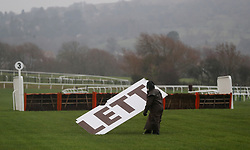 Groundstaff retrieve part of an advert board blown off in the high winds during day two of the International Meeting at Cheltenham Racecourse.