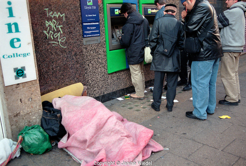 Homeless person asleep next to cash dispenser in Oxford Street Central London.