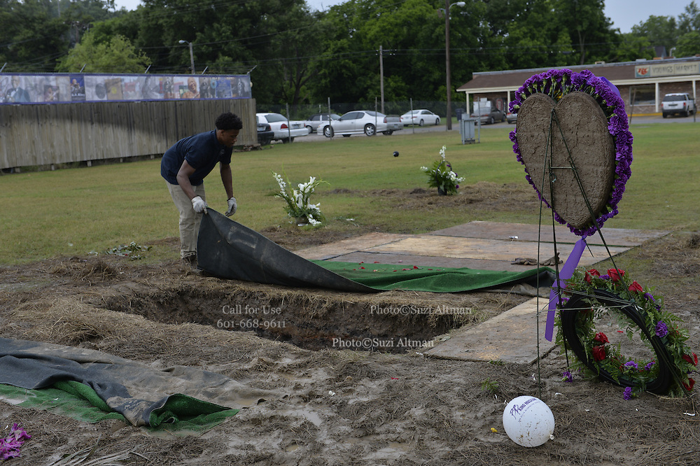 "5/30/15 Indianola, MS.  Fans wait in the rain to see B. B Kings final home coming funeral procession outside the BB King Museum. A family member reaches out to touch the casket for one last time at the gravesite of Mr. King during the burial outside in the rain. The Thrill is gone, the casket holding the body of BB King arrives at the Bell Grove Missionary Baptist Church for his final homecoming. Blues legend B.B. King is is laid to rest in the shadow of the cotton gin at the B.B. King Museum and Interpretive Center. Mr King's final homecoming procession included a black horse WITH A saddle flanked with two of BB's famous ""Lucielle"" guitars signed by Mr. King. Fans lined the streets to watch the procession and pay their respect to the King of the Blues. Photo ©Suzi Altman"