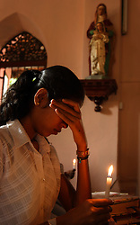 Ahalya Jothi Luxmi, 14, cries while she holds a candle for the nine members of her family killed in the tsunami, Batticaloa, Sri Lanka, Jan. 26, 2005. Residents of the small Christian village Dutch Bar spent more than six weeks in a makeshift refugee camp at the local convent recovering from the devastating tsunami that hit the eastern and southern borders of Sri Lanka. They were then moved into another temporary living camp, while awaiting the building of new homes. More than 150 members in this community of less than 1000 people died in the tragic event.