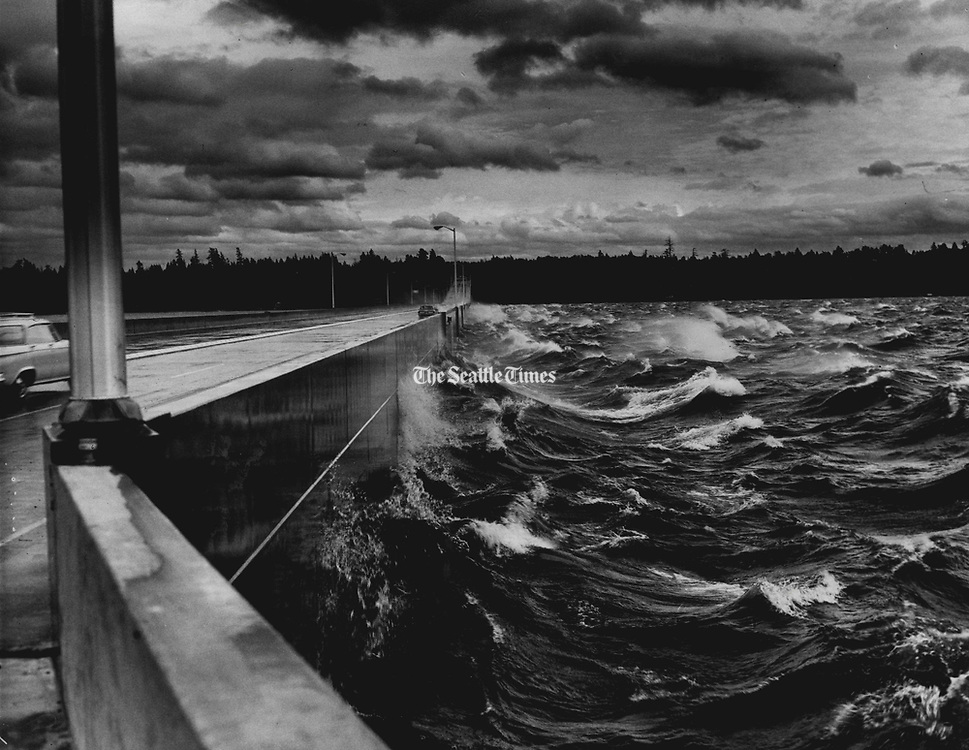Motorists may have felt slightly out to sea while driving across the Evergreen Point Floating Bridge. Winds up to 40 miles an hour churned Lake Washington and sent waves crashing over the rail-of the bridge. (Richard Heyza / The Seattle Times, 1963)