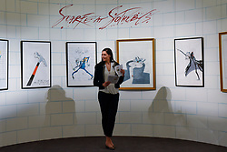 """© Licensed to London News Pictures. 31/03/2017. London, UK. A staff member stands in a wall containing works by Gerald Scarfe. The wall references Scarfe's contribution to Pink Floyd's """"Another Brick in the Wall"""".  Press preview of """"Made in Britain"""" at Sotheby's in New Bond Street.  The auction on 5 April celebrates innovative British art in the twentieth century as well as artwork by political cartoonist Gerald Scarfe. Photo credit : Stephen Chung/LNP"""