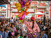 "09 AUGUST 2014 - BANGKOK, THAILAND:       An inflatable toy vendor sells to people waiting for free meals at the Ruby Goddess Shrine in the Dusit section of Bangkok. The seventh month of the Chinese Lunar calendar is called ""Ghost Month"" during which ghosts and spirits, including those of the deceased ancestors, come out from the lower realm. It is common for Chinese people to make merit during the month by burning ""hell money"" and presenting food to the ghosts. At Chinese temples in Thailand, it is also customary to give food to the poorer people in the community.   PHOTO BY JACK KURTZ"