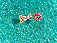 Aerial view of two young girls floating in sea on pizza and donut shaped inflatables touching feet.