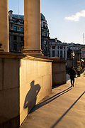 With most Londoners still working from home, a commuter leaves his shadow on a wall of Royal Exchange while walking along a quiet Threadneedle Street during the evening rush-hour during the third lockdown of the Coronavirus in the City of London, the capital's financial district, on 26th February 2021, in London, England.