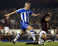 Photo: Chris Ratcliffe.<br />Arsenal v Wigan Athletic. Carling Cup. 24/01/2006.<br />Graham Kavanagh (L) of Wigan is tackled by Mathieu Flamini