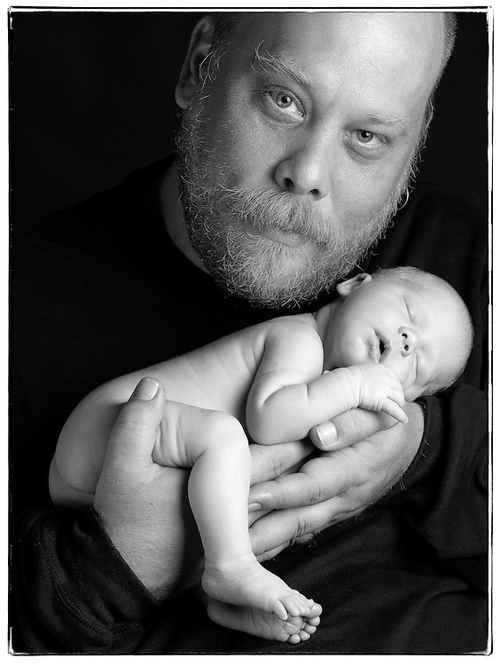 """Mr. Dwayne Kemp, composer and 3D creator with her """"two day old"""" little girl"""