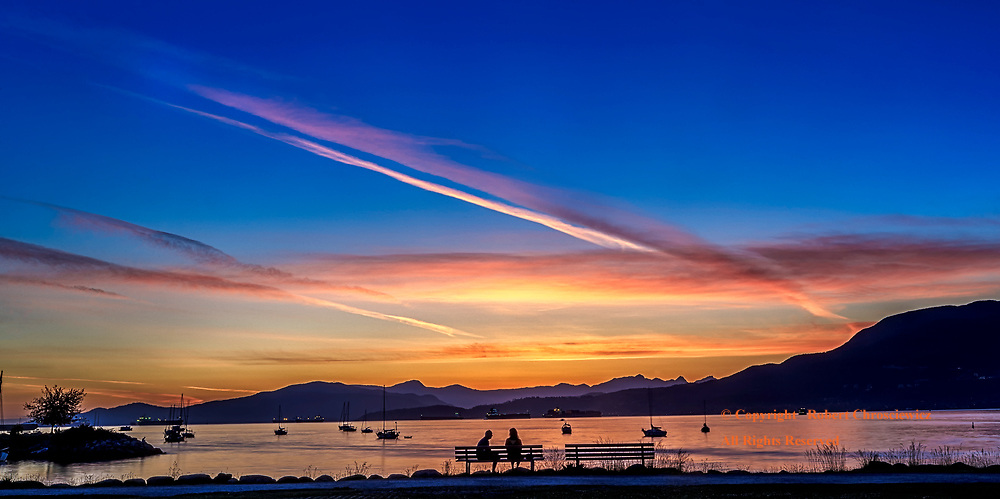 Kitsilano Evening: A couple sit seemingly oblivious to the vivid sunset, Vancouver British Columbia Canada.