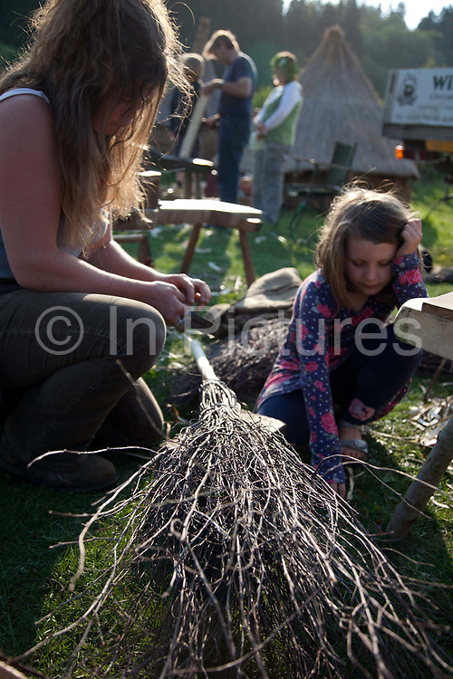 A young girl and her mother with a piece of willow. The annual Beltane celebrations at Butser ancient farm, Hampshire, marking the beginning of the British summer.