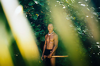 A portrait of a Chamorro seafarer, holding an axe he uses to build canoes in Guam.