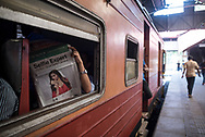A man reads the newspaper while waiting for his train to depart Fort railway station in Colombo, Sri Lanka. (April 1, 2017)