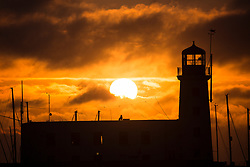 © Licensed to London News Pictures. 19/09/2017. Scarborough, UK. A bird perches on top of Scarborough light house as the sun breaks through a light layer of cloud at sunrise this morning. Photo credit: Andrew McCaren/LNP