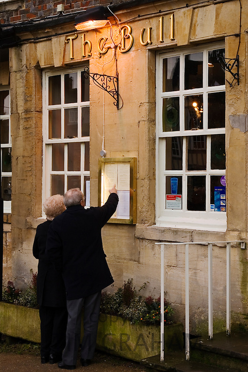 Couple read menu at The Bull pub and restaurant, Burford in the Cotswolds, Oxfordshire, UK