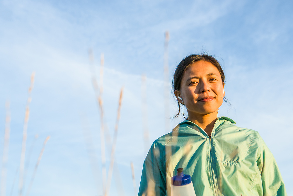 Portrait of a young Asian woman in outdoor activewear with ear buds in.