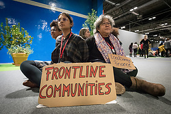 13 December 2019, Madrid, Spain: 'Frontline communities' reads a big sign, as people gather for a sit-in demonstration at COP25, to claim space for a range a groups whose voices are not often listened to in the space of global climate negotiations: youth, women, frontline communities, indigenous communities.