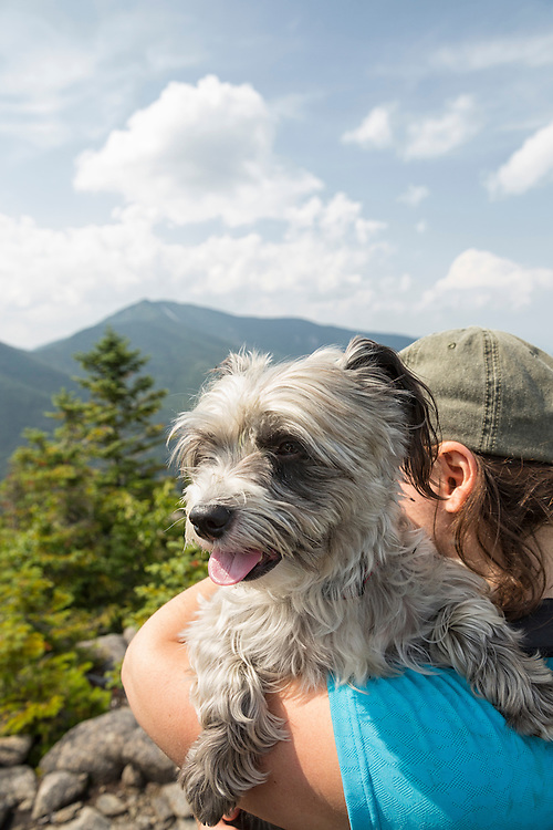 Owner holding small dog on the summit pf Grace Peak