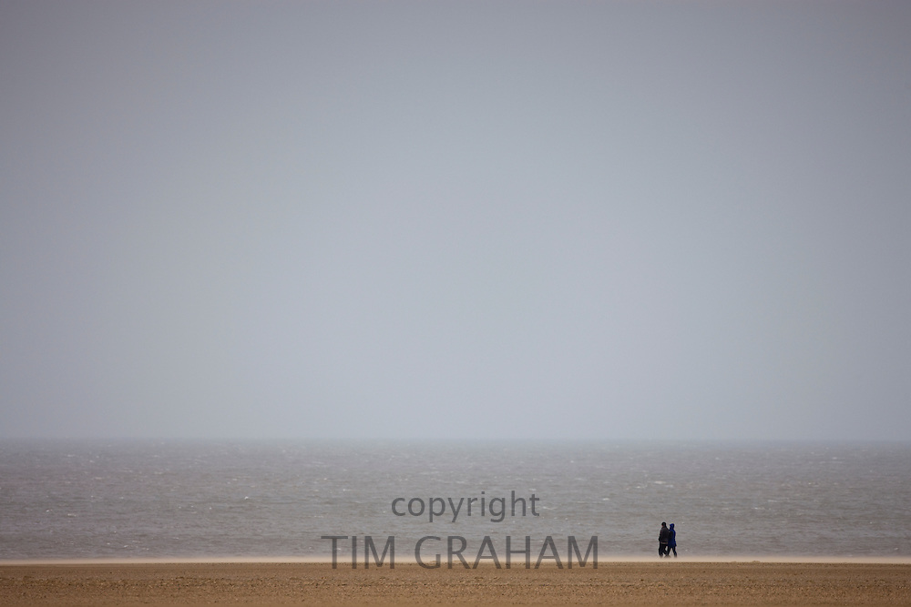Walkers stroll along the shoreline in wintertime at Holkham beach, North Norfolk, UK