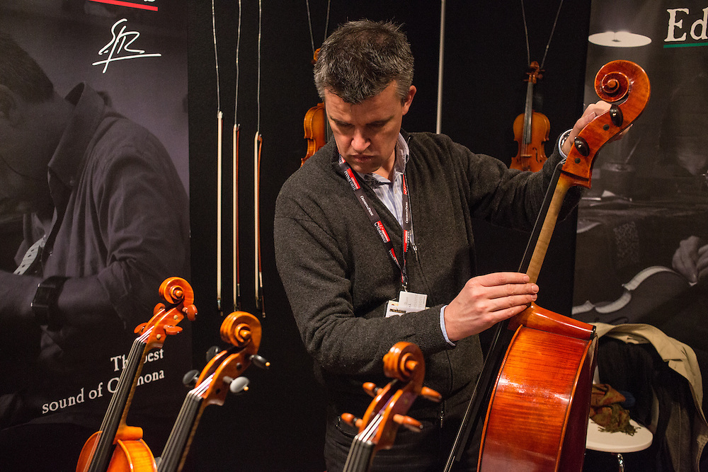 Edgar Russ, an Austrian-born luthier with a workshop in Cremona, tunes a cello.