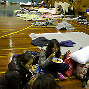 People settle in under a basketball scoreboard at the Crowles Stadium in Christchurch used to shelter earthquake victims.  A Powerful earth quake ripped through Christchurch, New Zealand on Tuesday lunch time killing at least 65 people as it brought down buildings, buckled roads and damaged houses, churches and the Cities Cathedral. 23rd February 2011.  Photo Tim Clayton