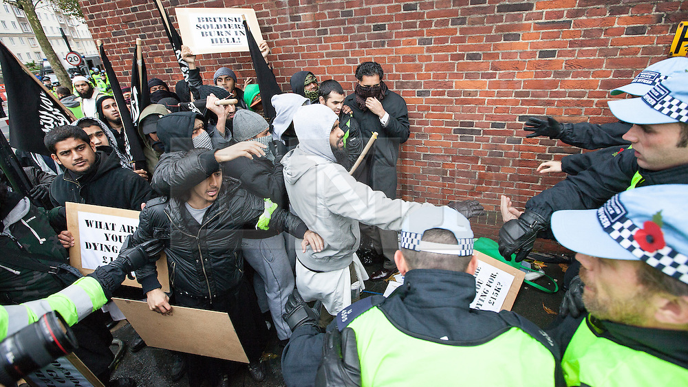 """© Licensed to London News Pictures . London , UK . Siddhartha Dhar (L holding a sign that reads """" What are you dying for , £15k ? """") during a scuffle with police at a Muslims Against Crusades demonstration on Exhibition Road in London on the anniversary of Armistice Day in London , on November 11, 2010. There has been speculation that Siddhartha Dhar is this the new 'Jihadi John', who appeared in a recent ISIS video. . Photo credit : Joel Goodman/LNP"""