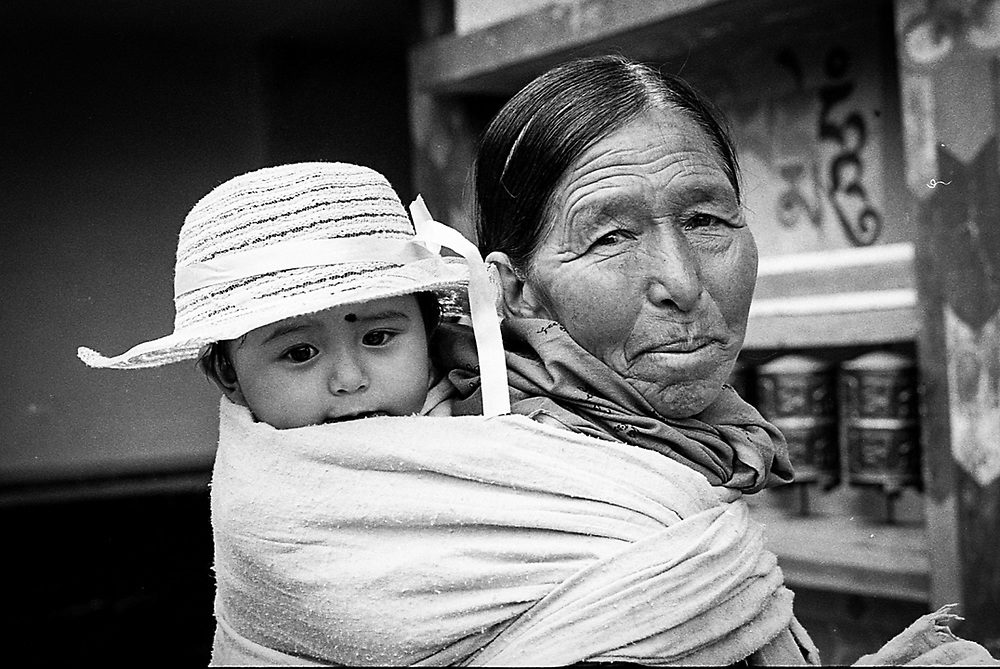 A grandmother is carrying her grandchild during a Buddhist festival at the Shasur Gompa of Keylong in Himachal Pradesh, India.<br /> Photo by Lorenz Berna
