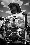 """Chávez supporter holds a poster of the late Venezuelan President during his funeral in Caracas, 8th March 2013. Chávez ruled Venezuela for 14 years, passed away on the 5th March 2013.  He revolutionized not only his nation but also other countries in Latin America, with his political views and what he called the """"21st Century Socialism"""", supported by the petrodollars from Venezuela's massive oil-reserves."""