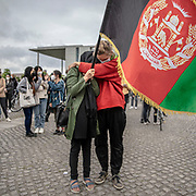 """A protester embraces an Afghan refugee as people take part in a demonstration in front the Reichstag  building, seat of the German lower house of Parliament, the Bundestag in Berlin, Germany, August 17, 2021. About 1000 people gathered in front of the  under the call """"Airlift now! Create safe escape routes from Afghanistan!"""", the spontaneous event was organized by Seebrücke and several other human-rights organizations."""