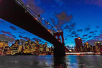 The Brooklyn Bridge and the skyline of Lower Manhattan at twilight from the East River, New York, New York USA.