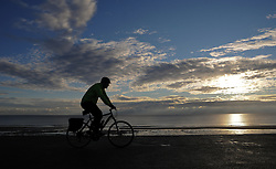 © Licensed to London News Pictures. <br /> 24/09/2014. <br /> <br /> Blyth, United Kingdom<br /> <br /> A cyclist rides along the promenade at dawn in Blyth, Northumberland.<br /> <br /> Photo credit : Ian Forsyth/LNP