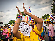 "05 AUGUST 2013 - BANGKOK, THAILAND: An anti-government ""white mask"" protestor applauds during an anti-government protest in Bangkok. About 500 people, members of the  People's Army against Thaksin Regime, a new anti-government group, protested in Lumpini Park in central Bangkok. The protest was peaceful but more militant protests are expected later in the week when the Parliament is expected to debate an amnesty bill which could allow Thaksin Shinawatra, the exiled former Prime Minister, to return to Thailand.    PHOTO BY JACK KURTZ"