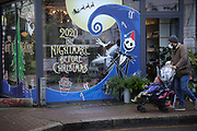 A shop window display says '2020 the Nightmare before Christmas' on 6th of December 2020, Hackney, London, United Kingdom. The words are a play on a Christmas film from the eighties, called 'Nightmare before Christmas' and is meant to make light hearted fun of the horrible year of 2020.  A child passing by with its father spots the skeleton man on the window.