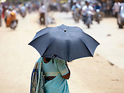 Woman holds umbrella to shield from the sun, Cochin, Kerala, India