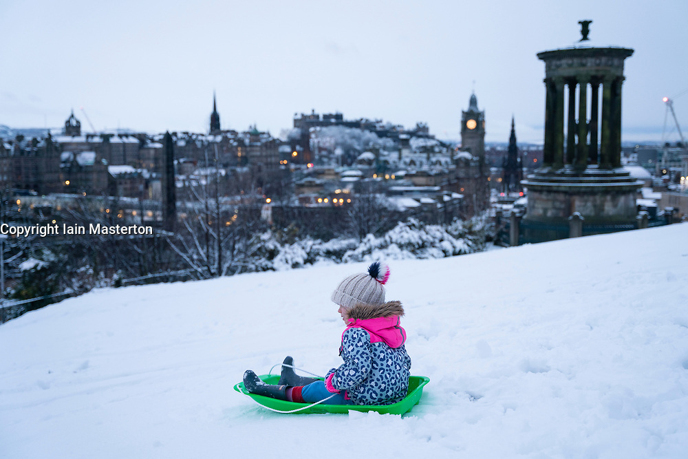 Edinburgh, Scotland, UK. 21 January 2020. Storm Christoph brought overnight snow to Edinburgh. Pic; Sisters Iris and Rosalie from Edinburgh enjoy sledging on Calton Hill in front of famous skyline view. Iain Masterton/Alamy Live News