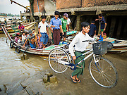 27 OCTOBER 2015 - YANGON, MYANMAR: A man gets off a cross river ferry with his bicycle at Aungmingalar Jetty in Yangon. The jetty is one of the numerous crossing points that bring people from the suburbs on the other side of the river into Yangon.    PHOTO BY JACK KURTZ