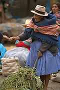 Woman paying vendor at market  Ollantaytambo, Peru