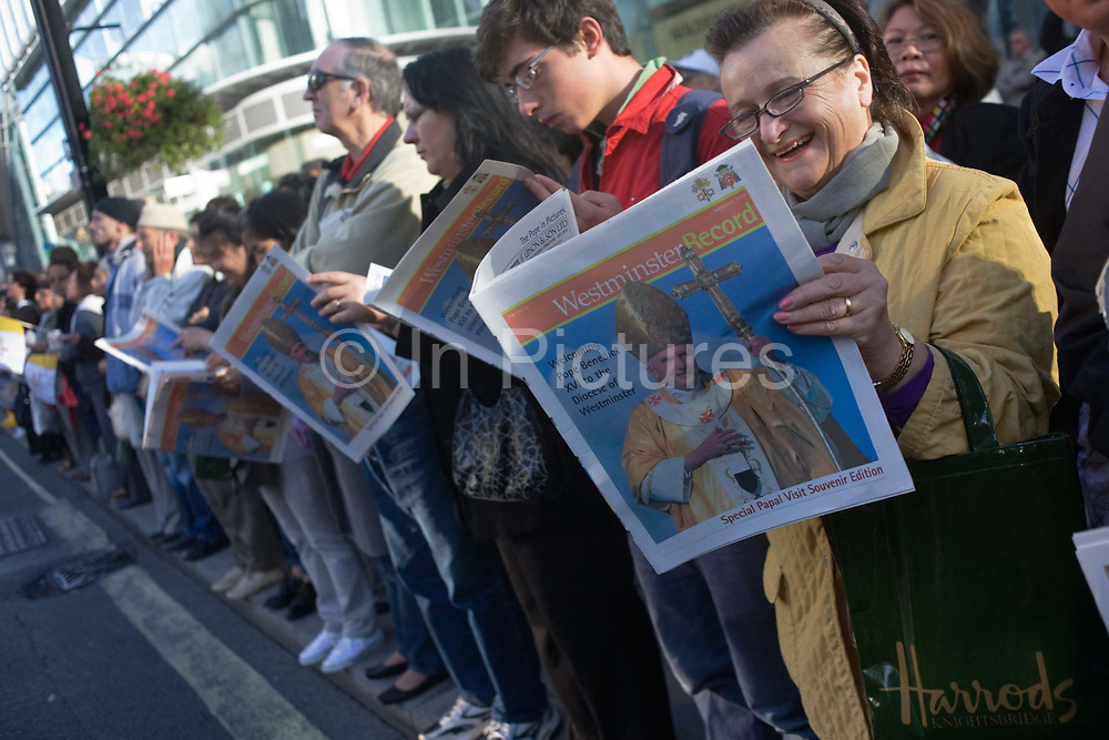 Catholics read free newspapers to crowds outside Westminster Cathedral before Pope Benedict XVI arrives during his papal tour of Britain 2010, the first visit by a pontiff since 1982. The lady in the foreground with the Harrods bag finds something amusing inside the paper standing on the kerbside in Victoria Street closed to traffic. Taxpayers footed the £10m bill for non-religious elements, which largely angered a nation still reeling from the financial crisis. Pope Benedict XVI is the head of the biggest Christian denomination in the world, some one billion Roman Catholics, or one in six people. In Britain there are about five million Catholics but only a quarter of Catholics regularly attend Sunday Mass and some churches have closed owing to spending cuts.