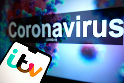 The ITV logo seen displayed on a mobile phone with an illustrative model of the Coronavirus displayed on a monitor in the background. Photo credit should read: James Warwick/EMPICS Entertainment