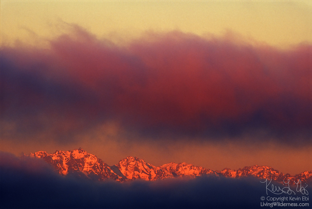Mount Constance, far left, and neighboring peaks in the Olympic Mountains of Washington state are visible between a layer of low clouds and fog. Mount Constance has an elevation of 7,756 feet (2,364 meters).