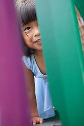 United States, San Francisco, girl (age 3) peeking through climbing structure in playground.  MR