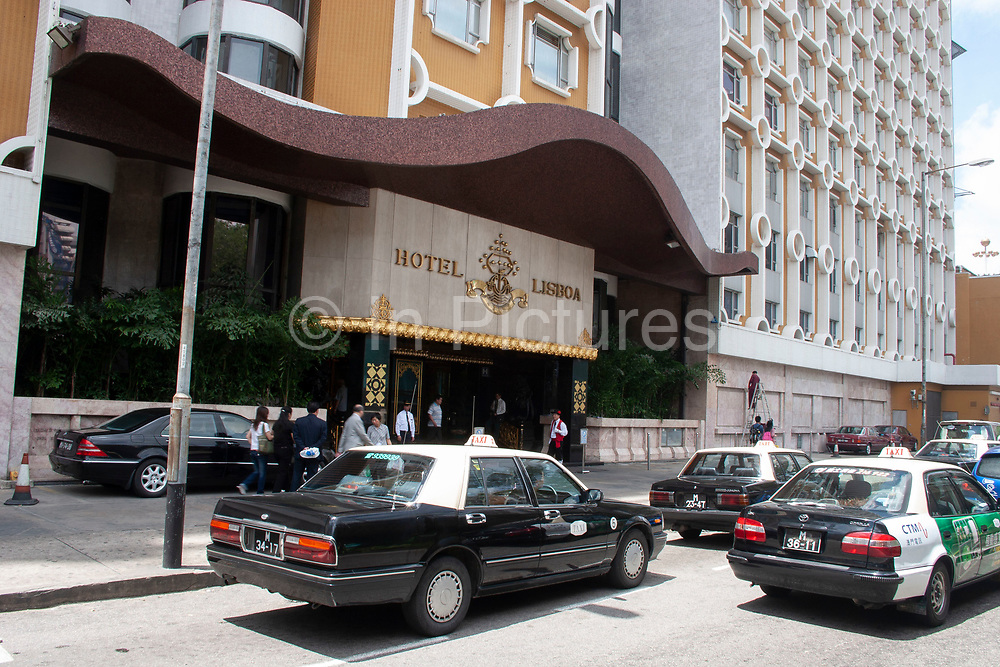 Taxis arrive outside Macaos famous, or some would say infamous Hotel Lisboa in Macao, China. Macao, is a haven for gamblers who travel on the fast ferries which run 24 hours a day fom Hong Kong. Punters come to this Portuguse influenced island to go to Casinos, banned in mainland China. Hotel Lisboa is an ornate place for people to escape into a world of gambling and with working girls roaming the corridors, prostitution.