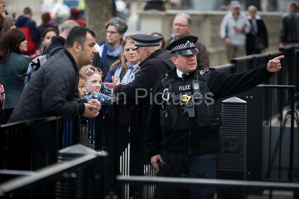 Diplomatic protection police officer interacting with tourists at the gates of Downing Street, the Prime Minister's address in Westminster London. Pointing up the street for the benefit of a male visitor, possibly to show him exactly where the Prime Minister's official home is, the policeman is seen to be wearing a stab-proof vest and yellow-handled taser on his chest. Childern follow his gaze, interested to know about this London landmark at the heart of the UK's government.