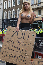 London, UK. 23rd August, 2021. A topless Extinction Rebellion activist poses with a sign during the first day of Extinction Rebellion's Impossible Rebellion protests in the Covent Garden area. Extinction Rebellion are calling on the UK government to cease all new fossil fuel investment with immediate effect. Credit: Mark Kerrison/Alamy Live News